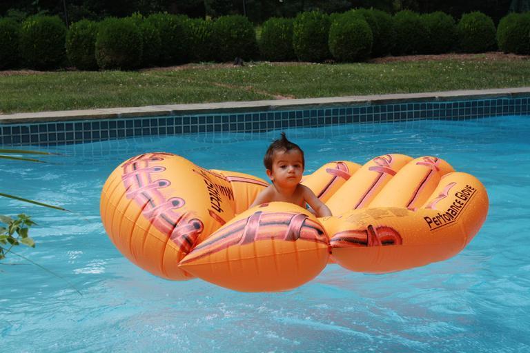 malé dítě v bazénu na oranžovém lehátku