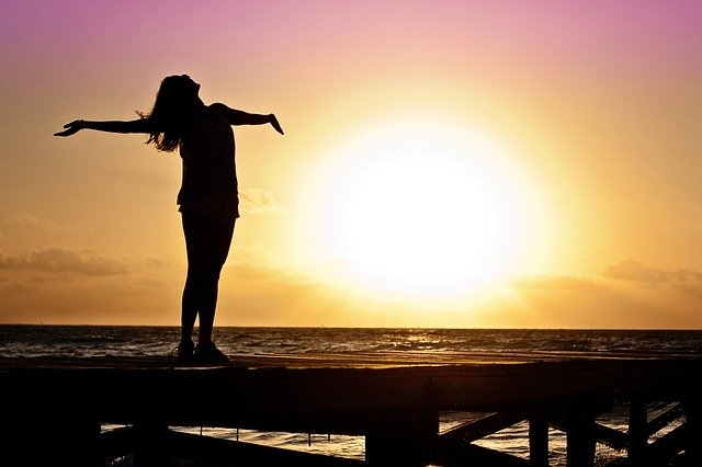 šťastná žena při západu slunce
